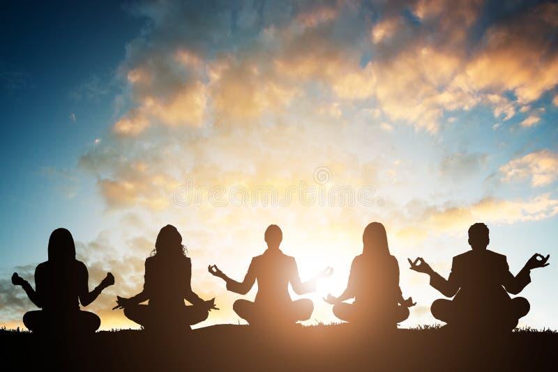 Grupo de pessoas que faz a ioga imagem de stock