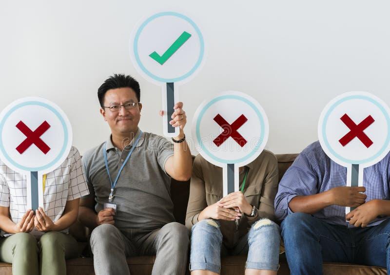 Grupo de pessoas que guarda ícones verdadeiros & falsos imagem de stock