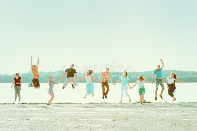 Grupo de pessoas que guarda as mãos e que salta no parque perto do lago Meninas e meninos de sorriso que têm o divertimento imagens de stock royalty free