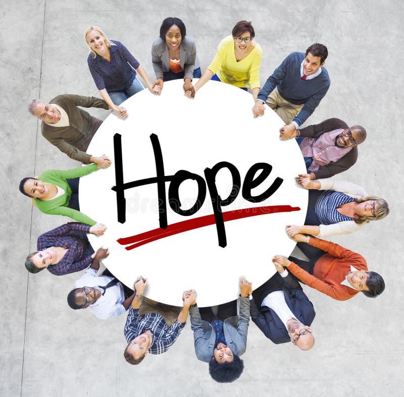 Grupo de pessoas que guarda as mãos em torno da esperança da letra imagem de stock royalty free
