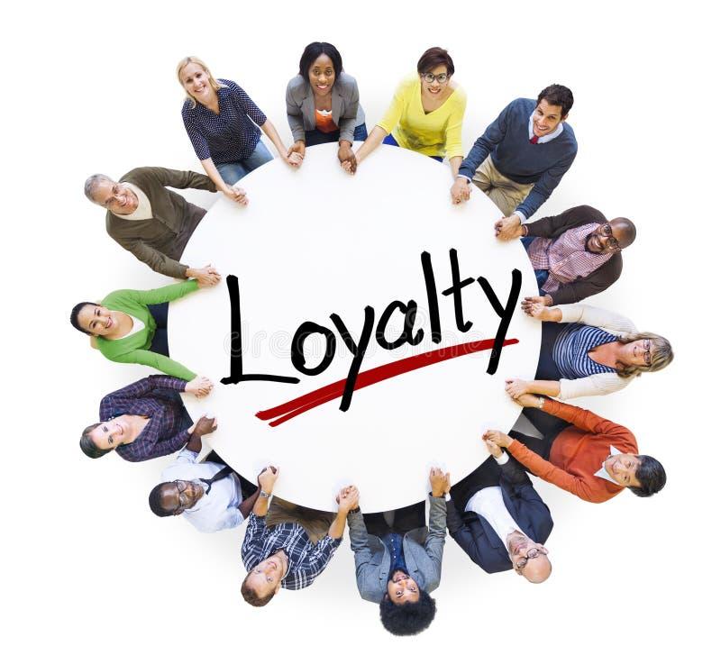 Grupo de pessoas que guarda as mãos em torno da lealdade da letra imagem de stock royalty free