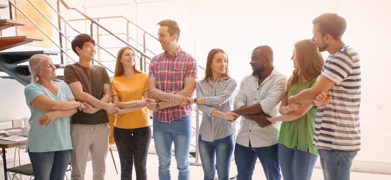 Grupo de pessoas que guarda as mãos no escritório Conceito da unidade foto de stock