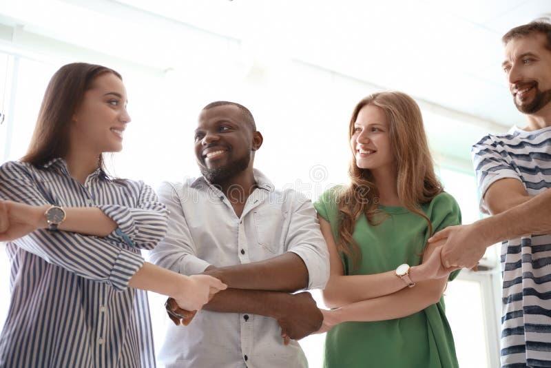 Grupo de pessoas que guarda as mãos no fundo claro Conceito da unidade imagem de stock