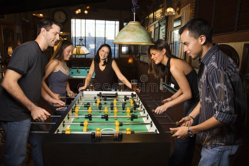 Grupo de pessoas que joga Foosball fotos de stock