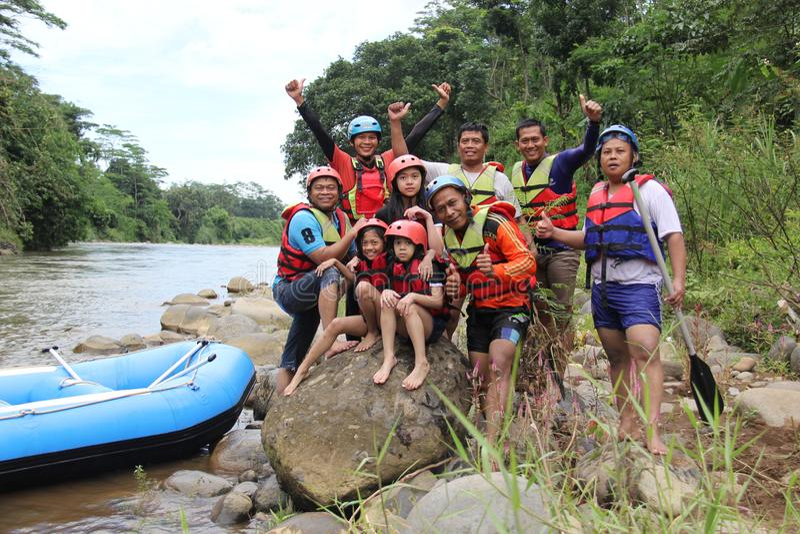grupo de pessoas que joga transportar em um rio que tenha um fluxo pesado, foto de stock
