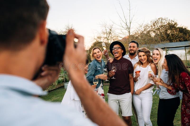 Grupo de pessoas que levanta para uma fotografia no partido imagem de stock
