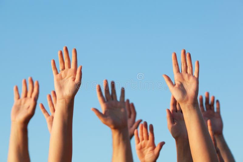 Grupo de pessoas que levanta suas mãos no ar fotos de stock