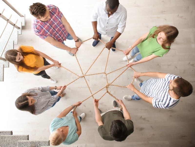 Grupo de pessoas que mantém a corda unida dentro, vista superior Conceito da unidade imagem de stock