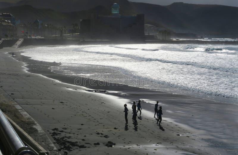 Grupo de pessoas que pratica no sol de nivelamento na praia em Las Palmas de Gran Canaria fotos de stock royalty free