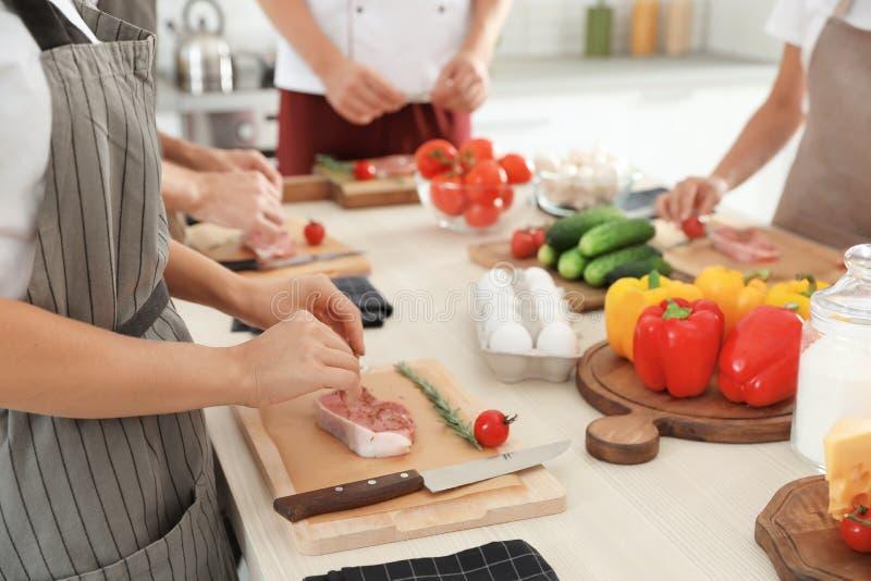 Grupo de pessoas que prepara a carne em aulas de culinária fotografia de stock