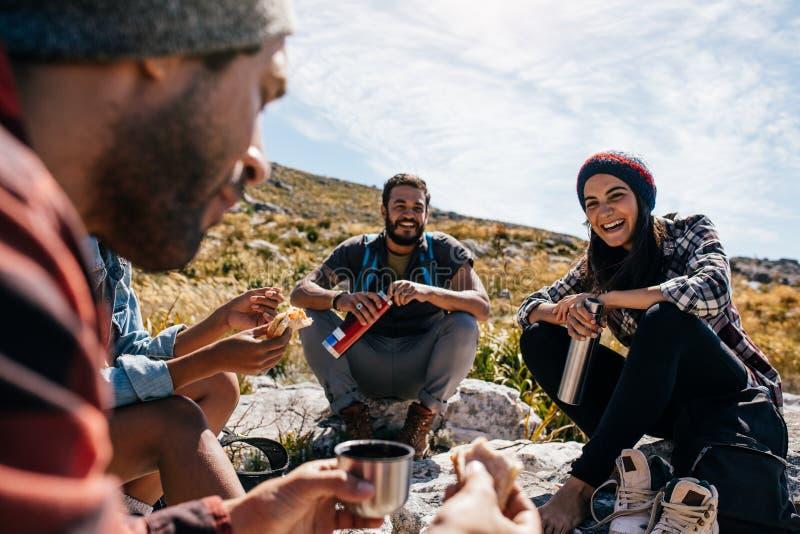 Grupo de pessoas que relaxa e que come durante a caminhada foto de stock