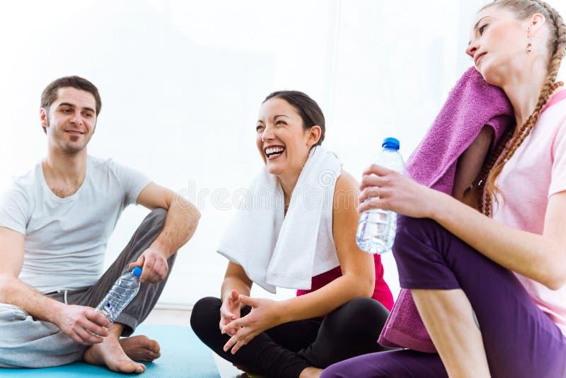 Grupo de pessoas que relaxa na esteira da ioga e que fala após o exercício s foto de stock