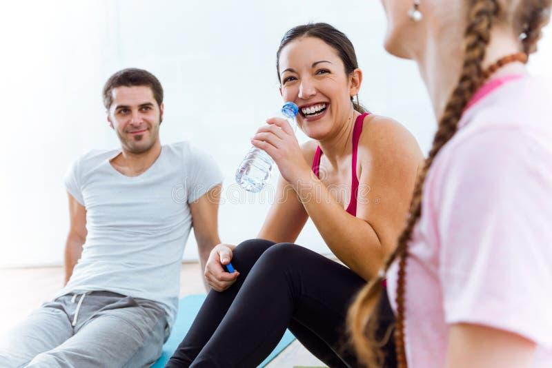 Grupo de pessoas que relaxa na esteira da ioga e que fala após o exercício s fotos de stock