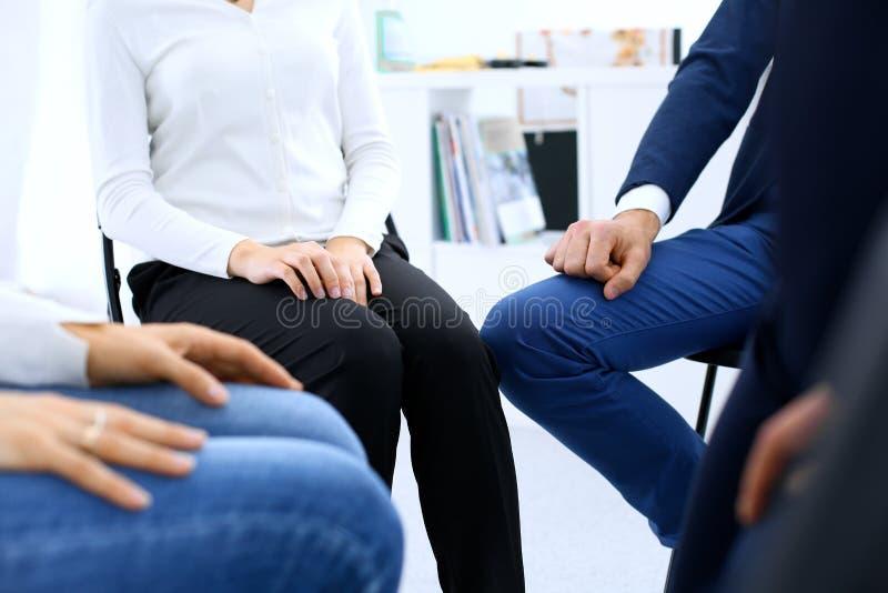 Grupo de pessoas que senta-se em um círculo durante a terapia Reunião da equipe do negócio que participa no treinamento imagem de stock