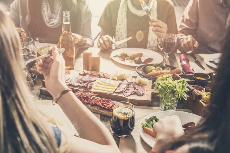 Grupo de pessoas que tem o jantar da unidade da refeição foto de stock royalty free