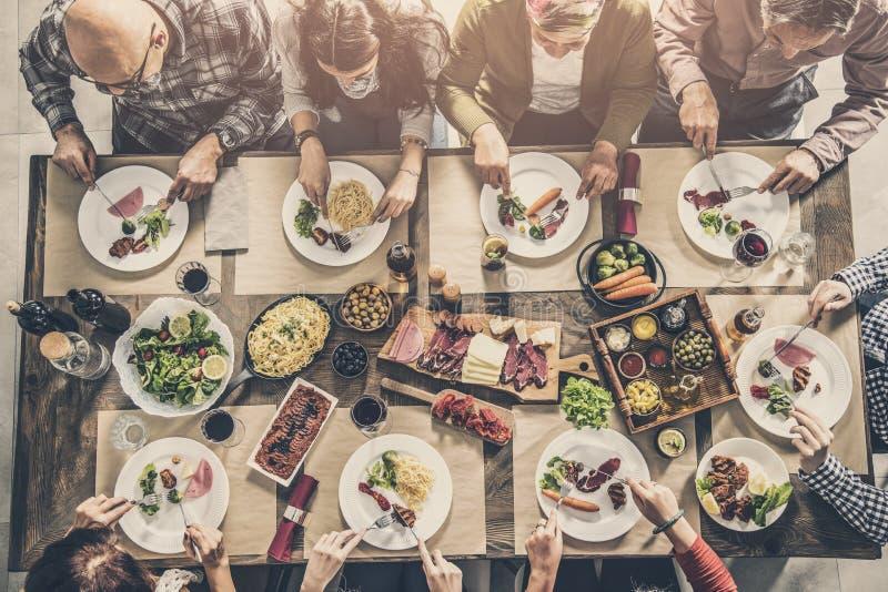 Grupo de pessoas que tem a refeição junto imagem de stock royalty free
