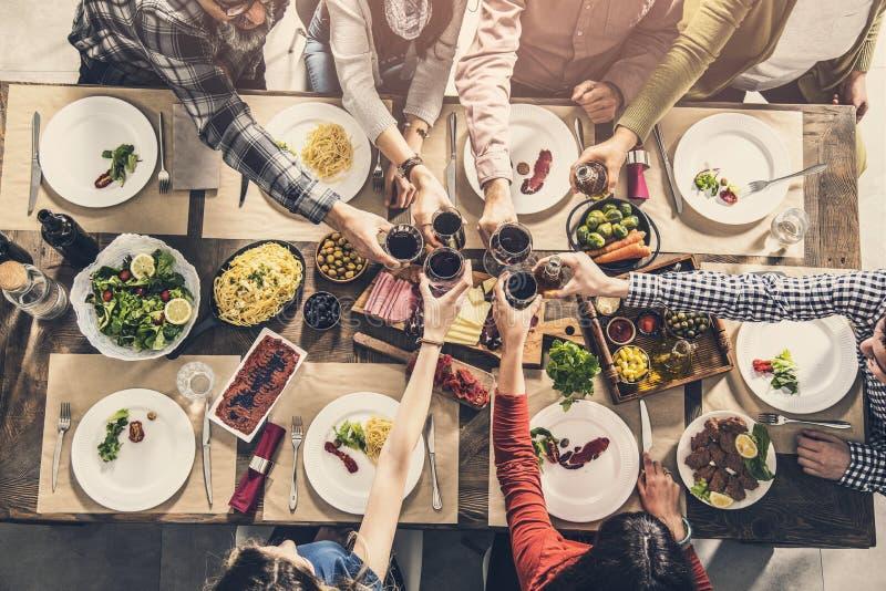 Grupo de pessoas que tem a unidade da refeição que janta brindando vidros imagens de stock