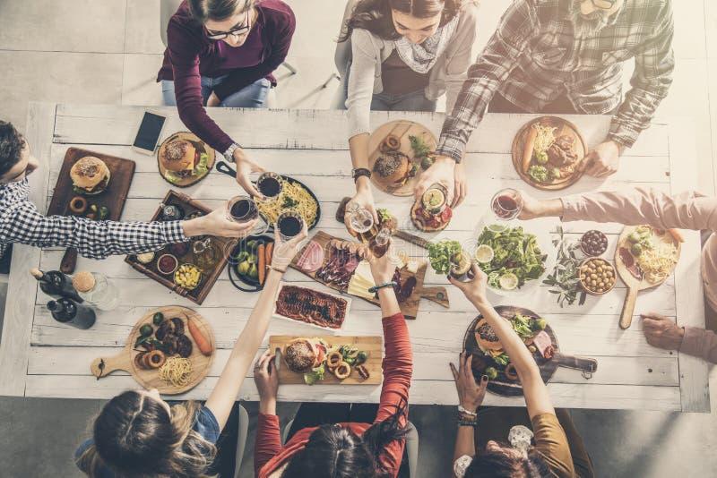 Grupo de pessoas que tem a unidade da refeição que janta brindando vidros fotos de stock royalty free
