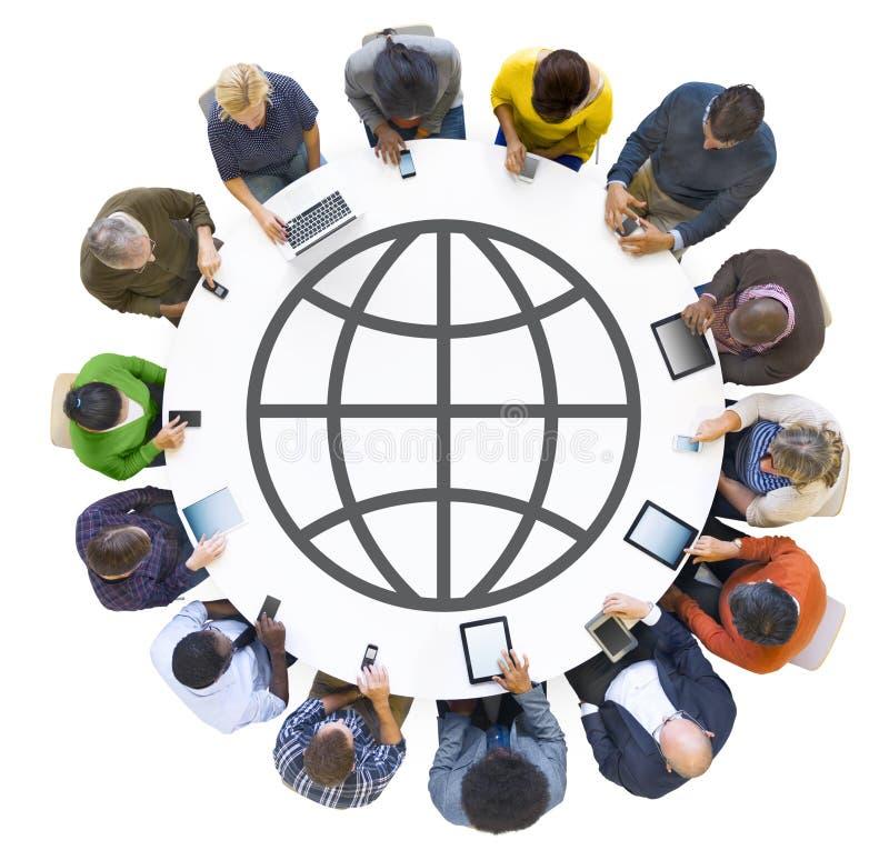 Grupo de pessoas que usa dispositivos de Digitas com símbolo global imagens de stock royalty free
