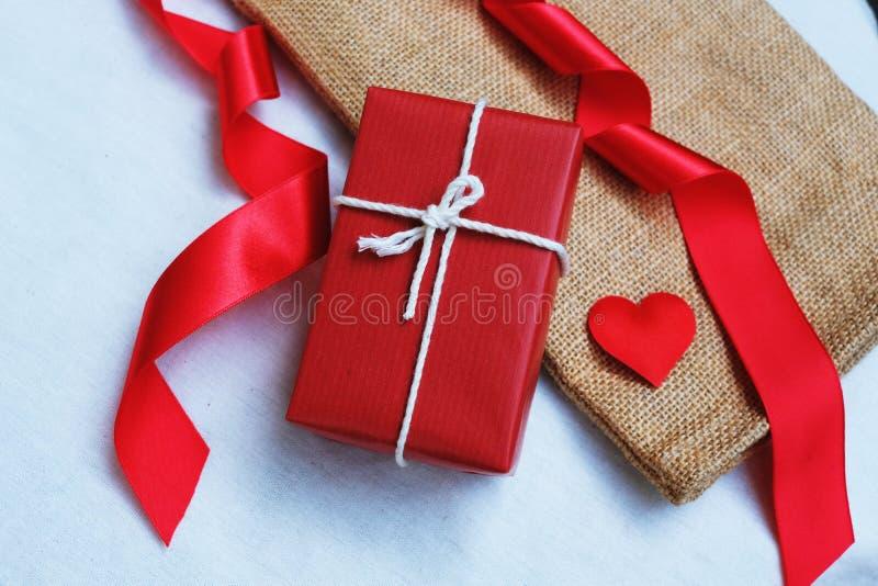 Grupo de pilha vermelha elegante da caixa de presente decorada com mini figura do cora??o no fundo de madeira, conceito atual bon imagens de stock royalty free