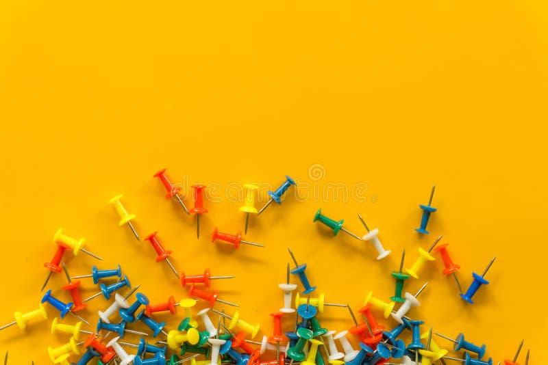 Grupo de pinos do impulso em cores diferentes thumbtacks Vista superior No fundo amarelo imagem de stock