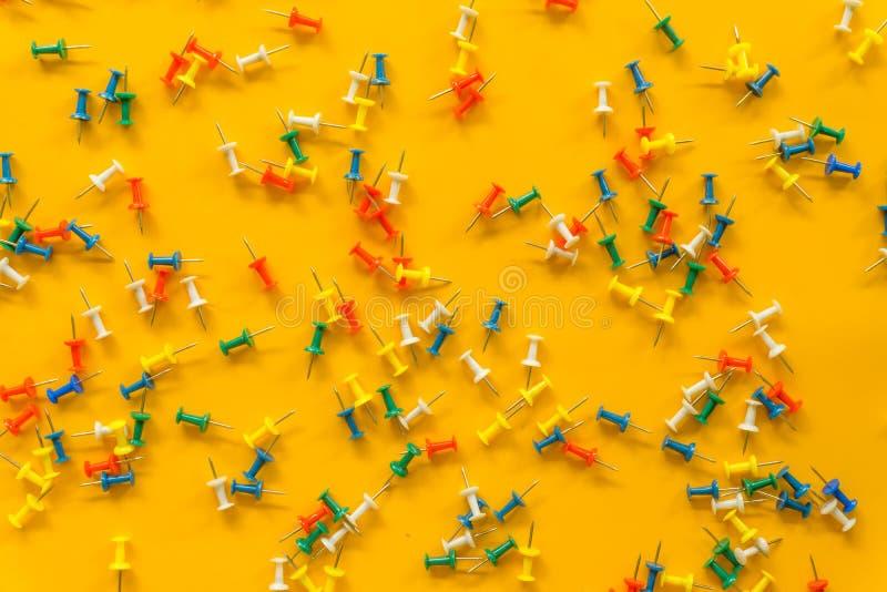 Grupo de pinos do impulso em cores diferentes thumbtacks Vista superior No fundo amarelo imagem de stock royalty free