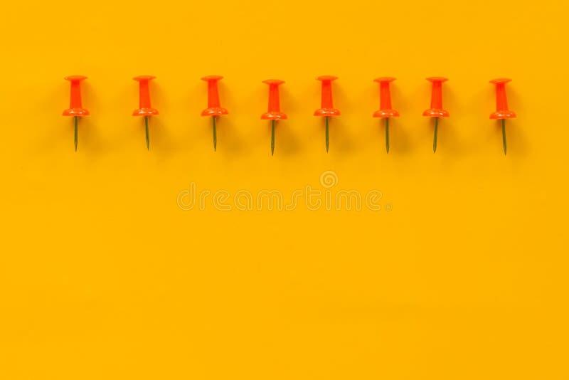 Grupo de pinos do impulso em cores diferentes thumbtacks Vista superior No fundo amarelo imagens de stock royalty free