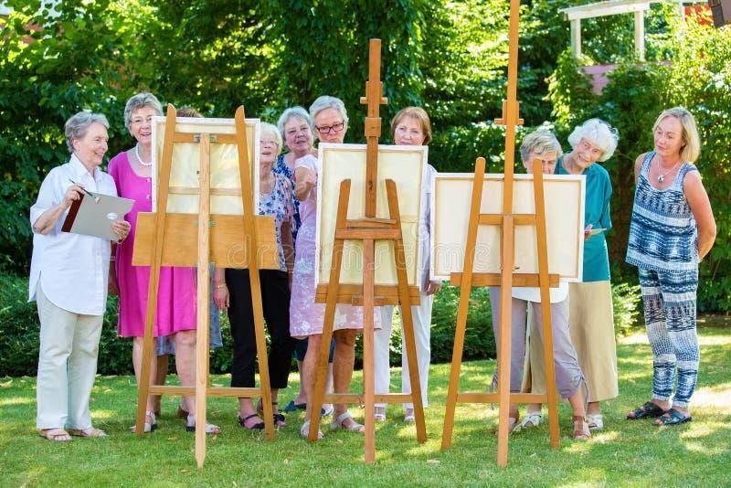 Grupo de pintura mayor sonriente de las mujeres en lona durante día soleado en jardín foto de archivo
