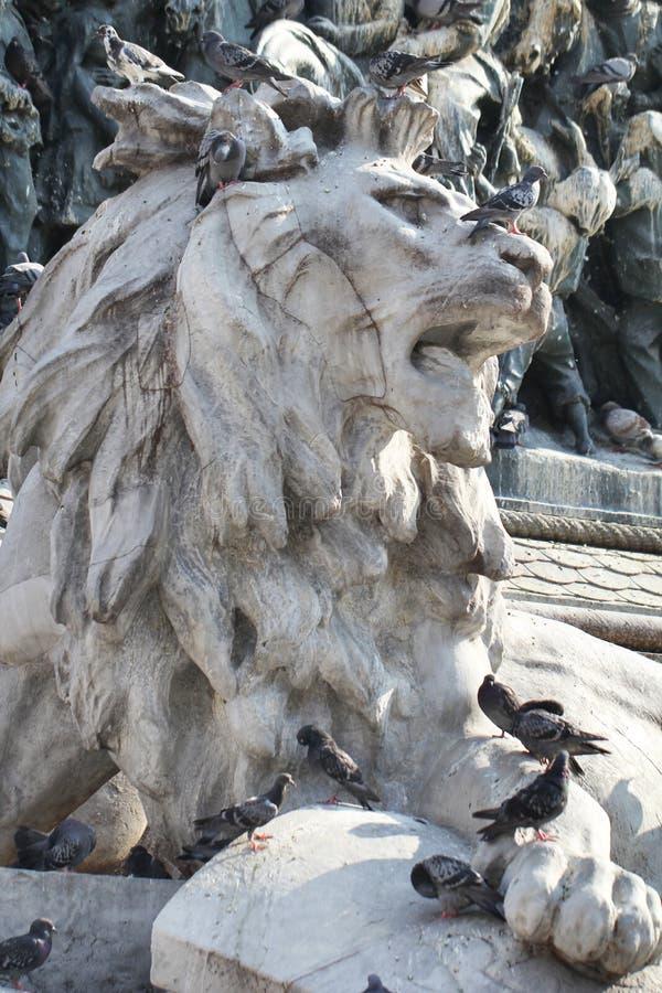 Grupo de pombos na estátua maravilhosa do leão em Piazza Duomo de Milão Itália, sujo da merda pooping do pássaro imagem de stock