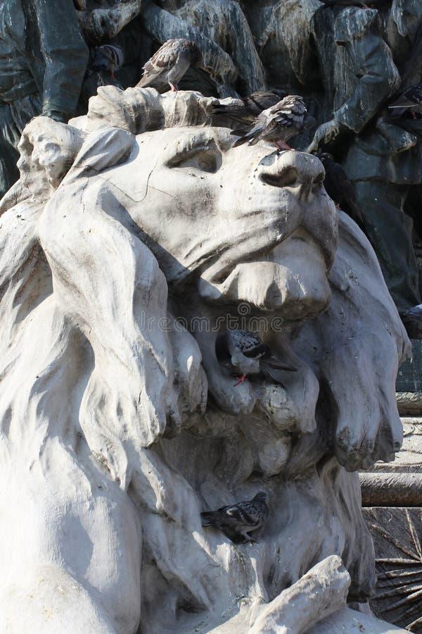 Grupo de pombos na estátua maravilhosa do leão em Piazza Duomo de Milão Itália, sujo da merda pooping do pássaro fotografia de stock
