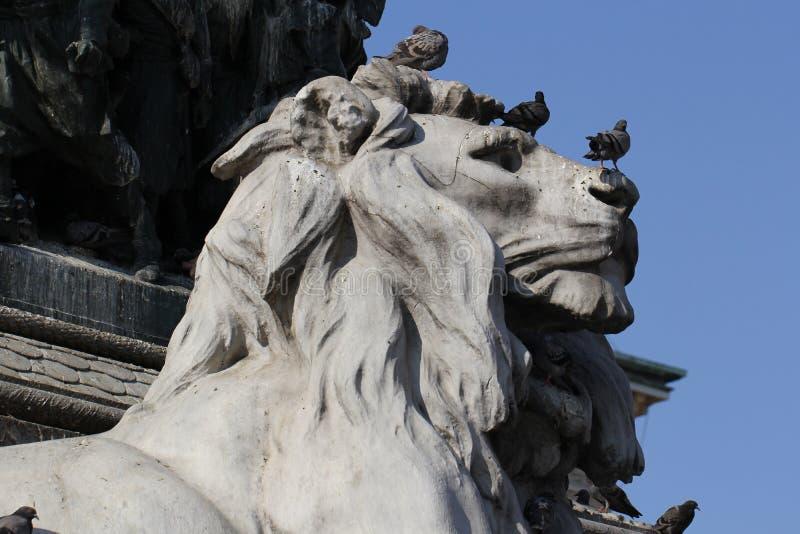 Grupo de pombos na estátua maravilhosa do leão em Piazza Duomo de Milão Itália, sujo da merda pooping do pássaro imagens de stock royalty free