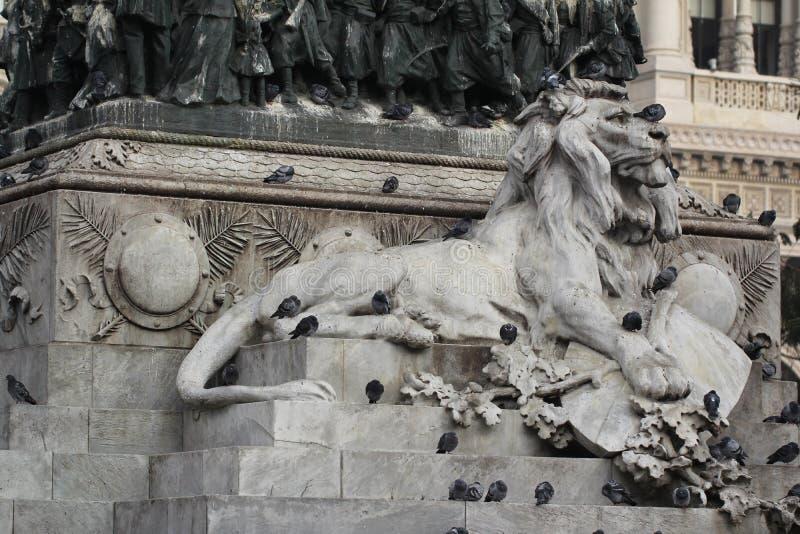 Grupo de pombos na estátua principal do leão em Piazza Duomo de Milão Itália, sujo da merda pooping do pássaro na arte atrativa d foto de stock