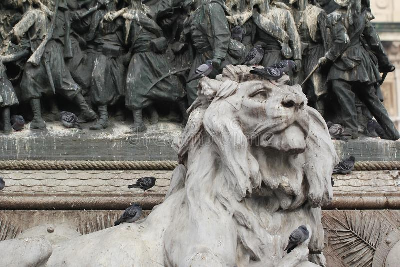 Grupo de pombos na estátua principal do leão em Piazza Duomo de Milão Itália, sujo da merda pooping do pássaro na arte atrativa d imagens de stock royalty free