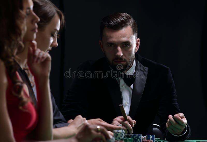 Grupo de povos à moda que jogam em um casino foto de stock