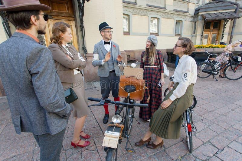 Grupo de povos antiquados do estilo na roupa do vintage que falam no festival do ciclismo em Europa imagens de stock