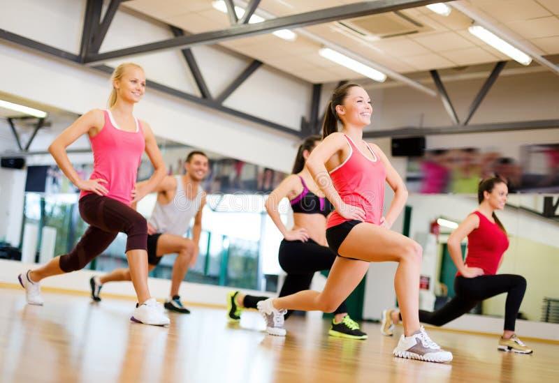 Grupo de povos de sorriso que exercitam no gym imagem de stock