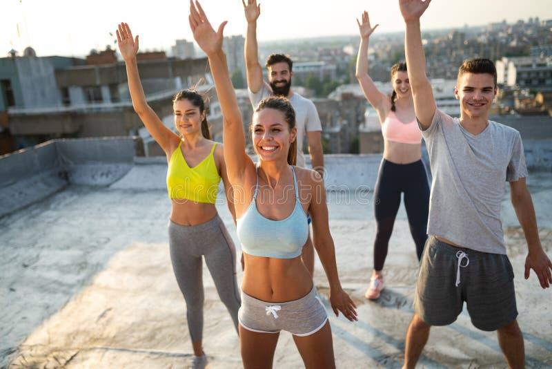 Grupo de povos desportivos felizes do ajuste que exercitam fora fotografia de stock