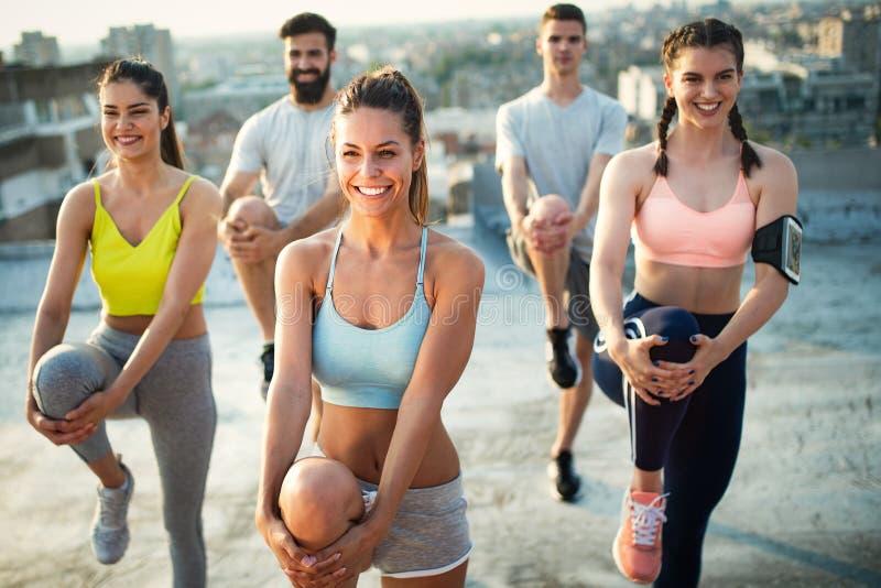Grupo de povos desportivos felizes do ajuste que exercitam fora fotos de stock royalty free