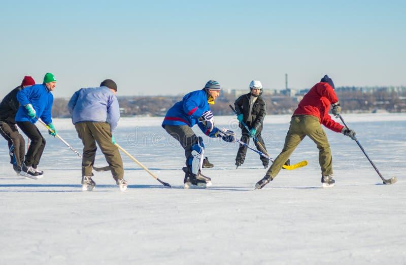 Grupo de povos diferentes das idades que jogam o hóquei em um rio congelado Dnepr em Ucrânia imagem de stock royalty free