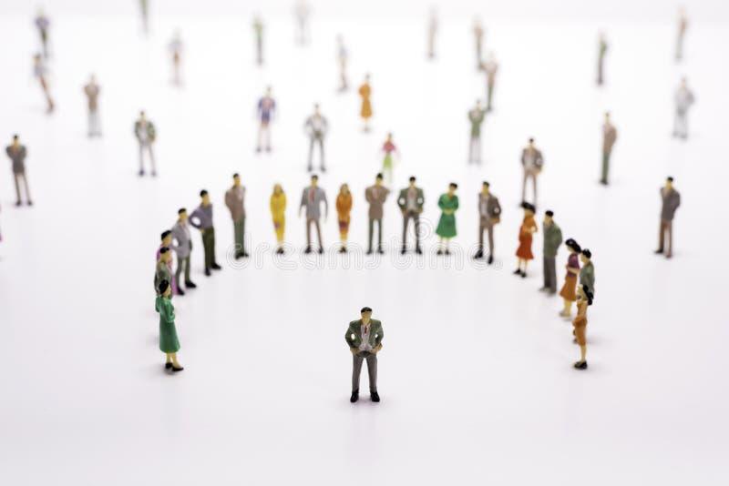 Grupo de povos diminutos sobre o fundo branco que está na linha fotografia de stock royalty free