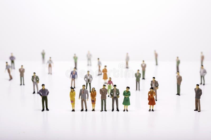 Grupo de povos diminutos sobre o fundo branco que está na linha fotos de stock royalty free
