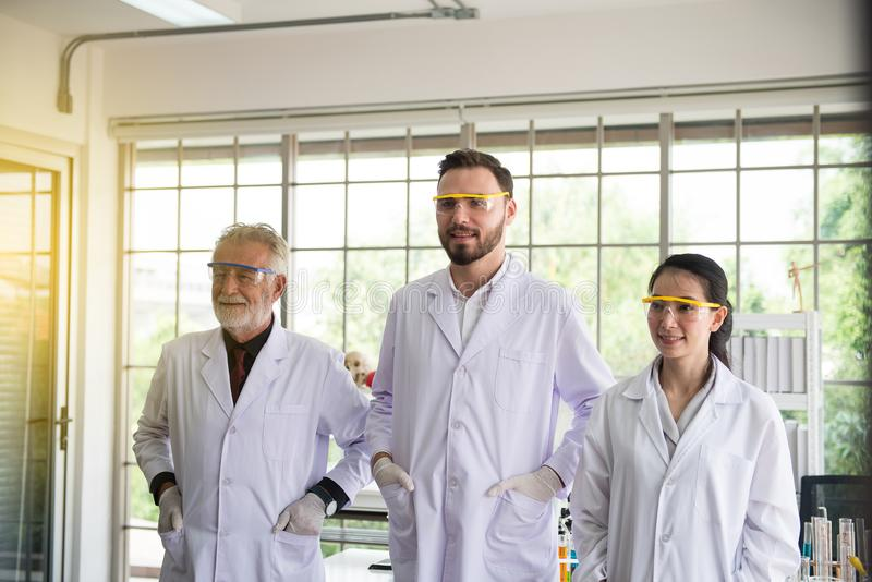 Grupo de povos dos cientistas que estão junto no laboratório, em trabalhos de equipe bem sucedidos e em funcionamento do reserch imagem de stock royalty free