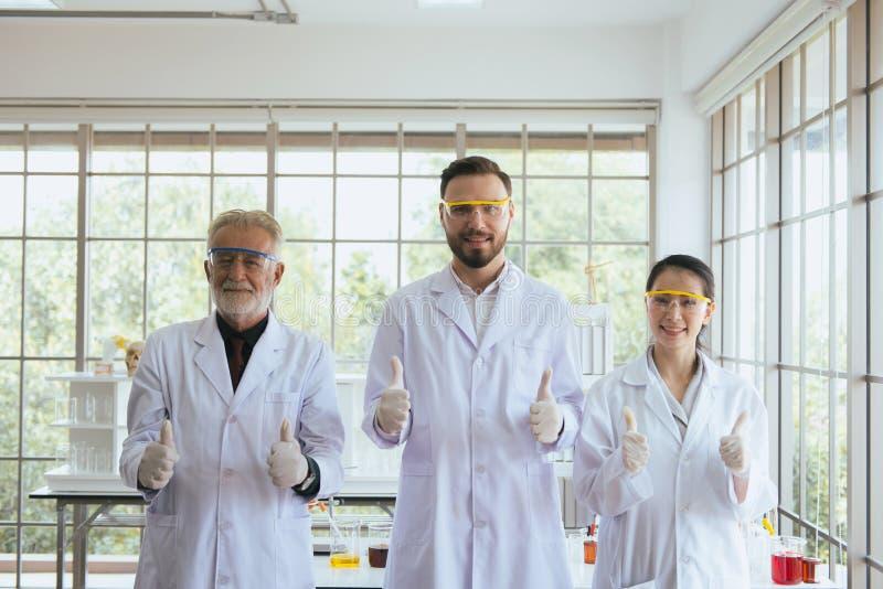 Grupo de povos dos cientistas que levantam-se e que mostram o polegar junto no laboratório, em trabalhos de equipe bem sucedidos  fotografia de stock royalty free