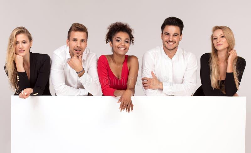 Grupo de povos elegantes com placa branca vazia foto de stock royalty free