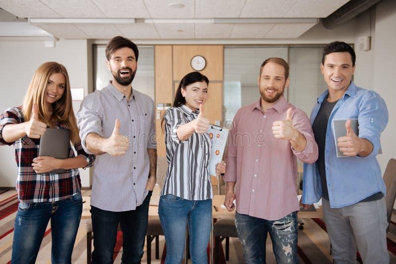 Grupo de povos felizes que aumentam os polegares acima fotografia de stock royalty free