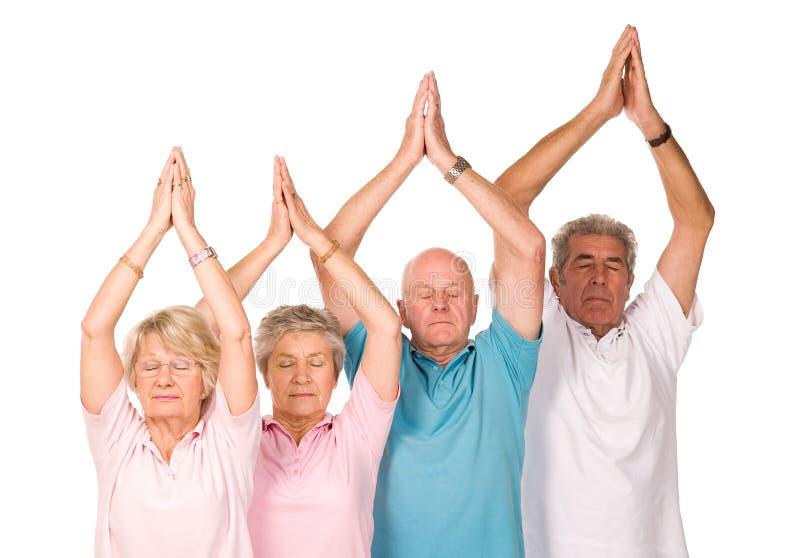 Grupo de povos maduros que fazem a ioga foto de stock