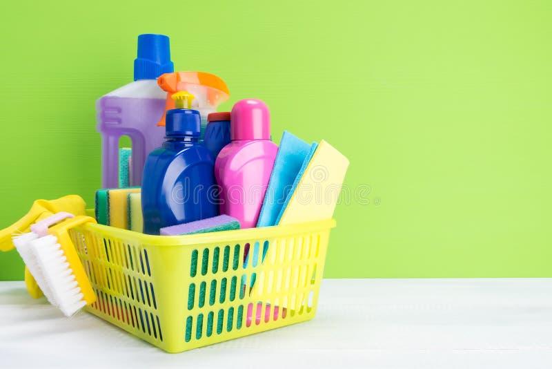 Grupo de produtos e de detergentes de limpeza para limpar em uma cesta amarela em um fundo verde, um lugar para sua inscrição fotografia de stock