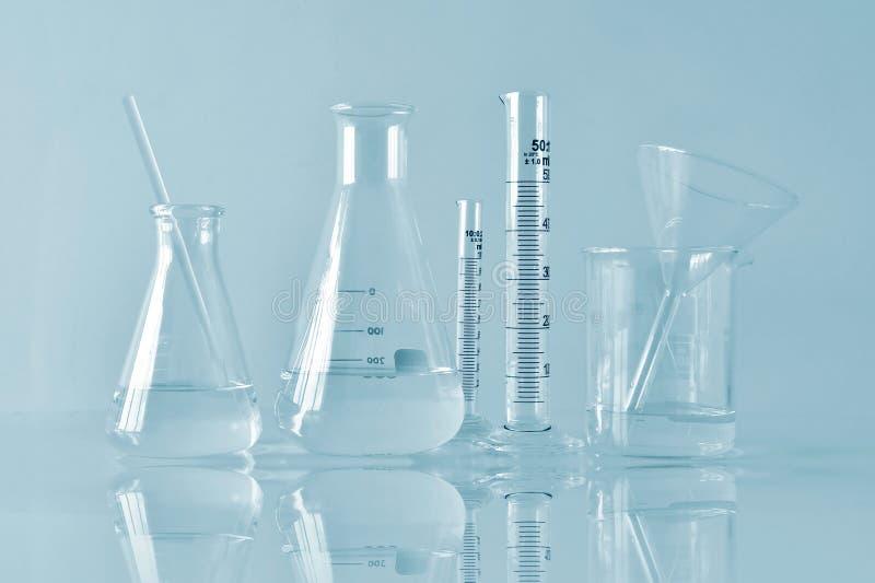 Grupo de produtos vidreiros de laboratório científicos com solução líquida clara, investigação e desenvolvimento fotografia de stock