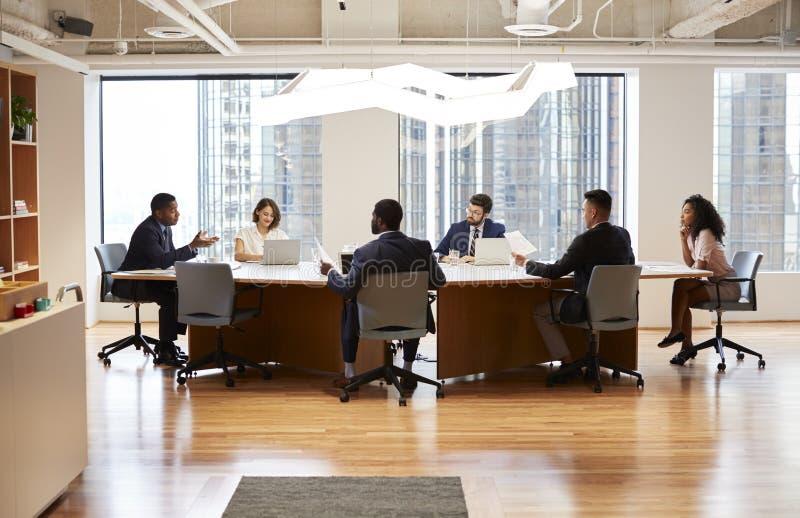 Grupo de profesionales del negocio que se encuentran alrededor de la tabla en oficina moderna foto de archivo libre de regalías