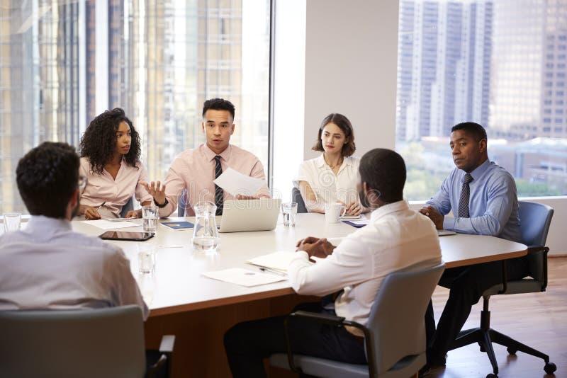 Grupo de profesionales del negocio que se encuentran alrededor de la tabla en oficina moderna imágenes de archivo libres de regalías